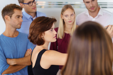 gruppe im büro hört einer kollegin zu