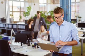 mitarbeiter steht im büro und schaut auf seinen laptop