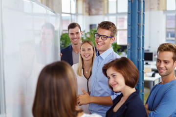 lachendes team in einer besprechung am flipchart