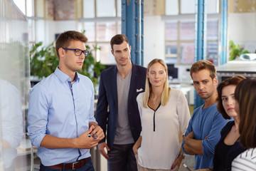 team im büro schaut mit ernstem gesichtsausdruck