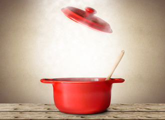 Big red pot for soup with spoon and fork