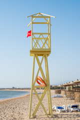 Shore on the sand a wooden tower and rescue lifeline. Vertical