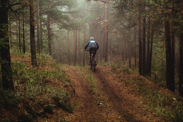 man racer mountain biking autumn forest in fog. race mountain bike
