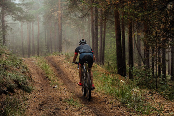 man mountain biking autumn forest in fog. concept healthy lifestyle and active recreation