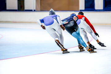 three athletes skating on ice sports arena. warm-up before competitions in speed skating