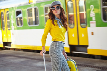 Beautiful young woman with suitcase is waiting a train