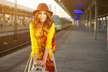 Pretty young woman at a train station (autumn toned image)