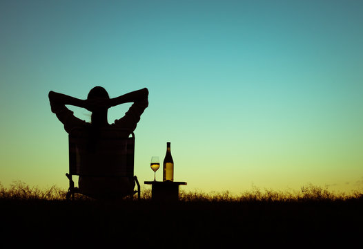 Woman relaxing watching the sunset and enjoying a glass of wine.