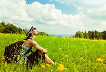 Girl relaxing in a field enjoying nature.