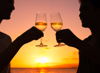 Life's happy moments. Couple celebrating with a glass of wine against a beautiful sunset.