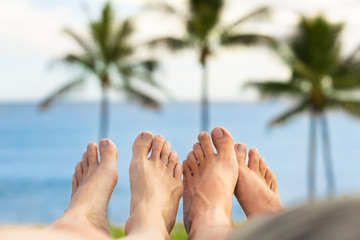 Couples feet relaxing by the sea.