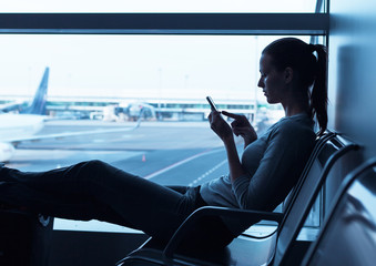 Woman traveler using smartphone at airport.
