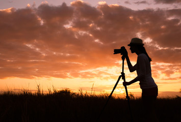 Female photographer capturing a beautiful sunset.