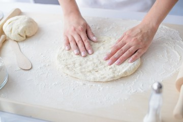 Woman kneading pizza dough on wooden pastry board.