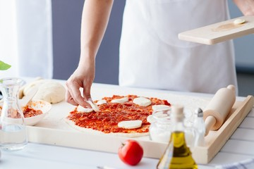 Woman puts slices of mozzarella on the pizza