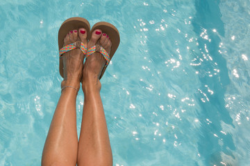 Woman legs with red nail ans shoes in swimming pool