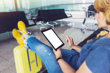Young hipster girl sitting at airport in yellow boot on suitcase traveling in Europe, female hands texting message on gadget in terminal area hall, summer trip concept, mockup blank screen tablet