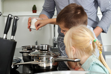 Small boy with girl salting food with  father in the kitchen