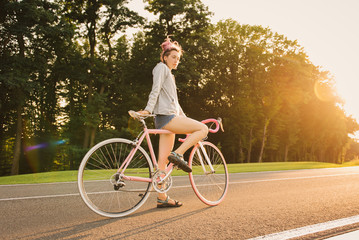 stylish women riding the bicycle on the road