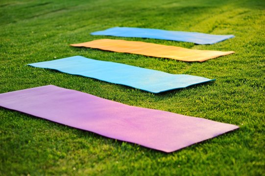 four yoga mats on the green with fresh grass