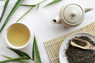 teapot and cup of herbal green tea on bamboo with white table background. over light