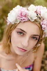 Young girl in flower wreath walking in meadow