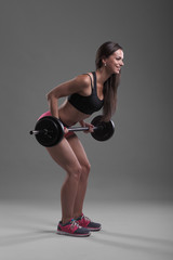 Girl with a barbell on grey background