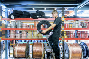 Worker choosing product from shelf in cable factory