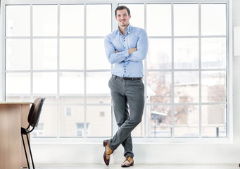 Confident businessman standing in office. Successful businessman