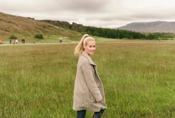 Blonde woman walking in grass