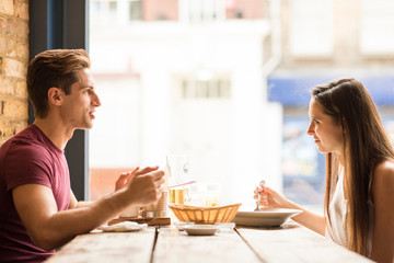 Young couple chatting whilst eating in restaurant