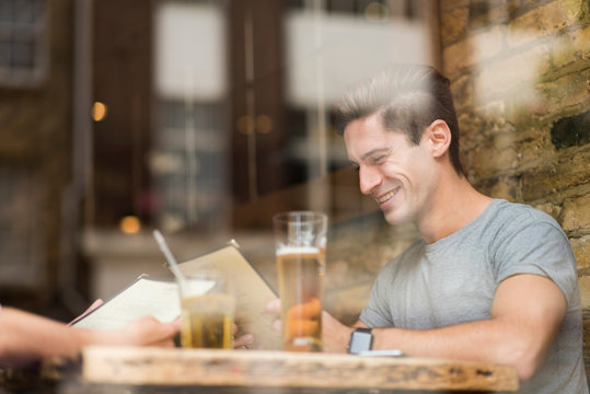 Window view of young man reading menu in restaurant