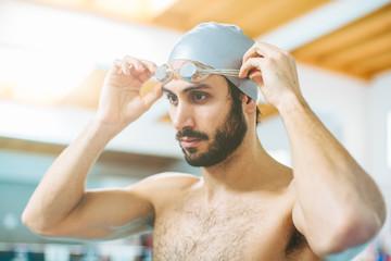 Man putting on swimming goggles