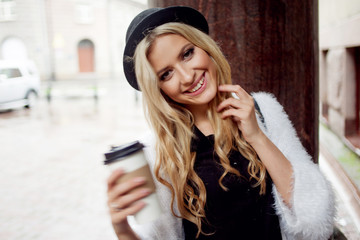 Cheerful woman in the street drinking morning coffee. Walking girl