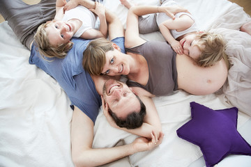 Pregnant mother with family, lying on bed
