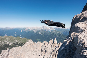 Base jumper flying over mountains