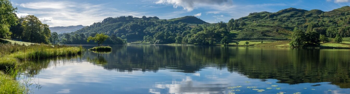 Wide panorama at Rydal Water in the Lake District on a calm summer morning.