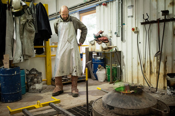 Male foundry worker putting on aluminium coated apron in bronze foundry