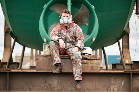 Portrait of worker in protective mask sitting in shipyard