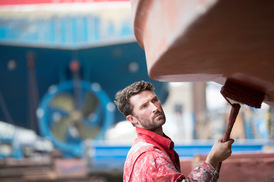 Male worker painting ship bottom in shipyard