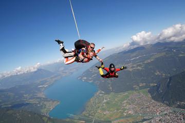 Smiling tandem sky divers holding hand with free faller, Interlaken, Berne, Switzerland