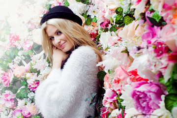 Young beautiful blonde woman in fashionable hat on floral background