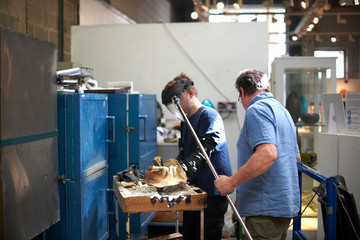 Glassblowers in workshop wearing protective gloves forming glass