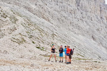 Hikers at bottom of rocky mountain, Austria