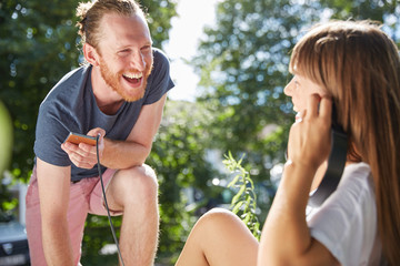 Young couple outdoors, listening to music through earphones