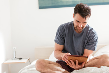 Man sitting in bed with tablet computer