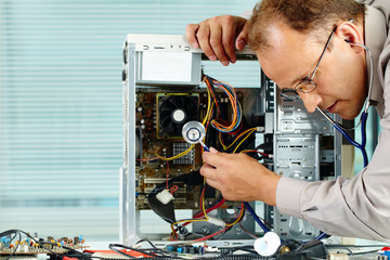 Computer engineer examining computer with stethoscope