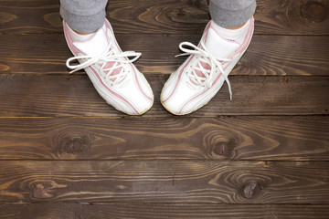 Girl sitting on a wooden floor. the view from the top. White sneakers on a dark wooden background.
