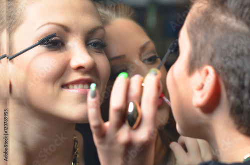Two Happy Teenage Girls Putting On Make Up In Front Of Mirror Before