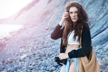 Girl in style of boho with a camera at sea
